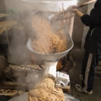 Miso making: Still hot, the steamed soybeans are put through a grinder to make a paste that is shaped into rounded loaves.  | SHOGO OIZUMI
