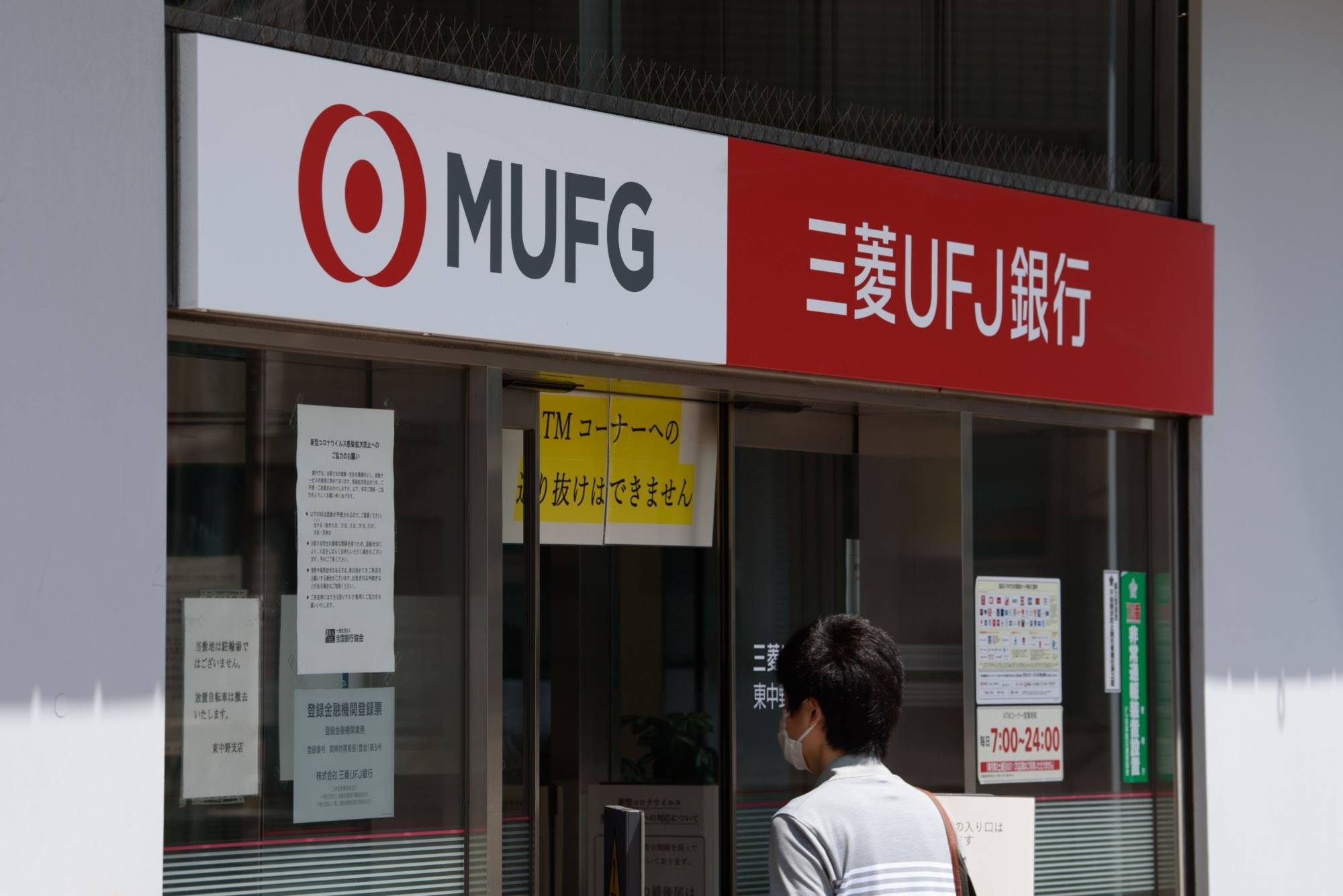 A customer enters a branch of MUFG Bank Ltd., a unit of Mitsubishi UFJ Financial Group Inc., in Tokyo. | BLOOMBERG