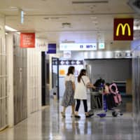 Passengers push a luggage cart in a nearly empty shopping and dining area at Narita Airport in Chiba Prefecture in July.  | BLOOMBERG