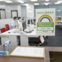 A COVID-19 safety sticker issued by the Tokyo Metropolitan Government is displayed in the Ikebukuro district of Tokyo.  | BLOOMBERG