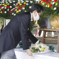Prime Minister Shinzo Abe lays flowers at Chidorigafuchi National Cemetery in Tokyo on Saturday as Japan marked 75 years since its surrender in World War II. | KYODO