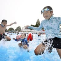 Children cool off in a pool in Tokyo's Nerima Ward.  | KYODO