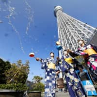Women sprinkle water to counter the summer heat at the foot of Tokyo Skytree on Saturday. | KYODO