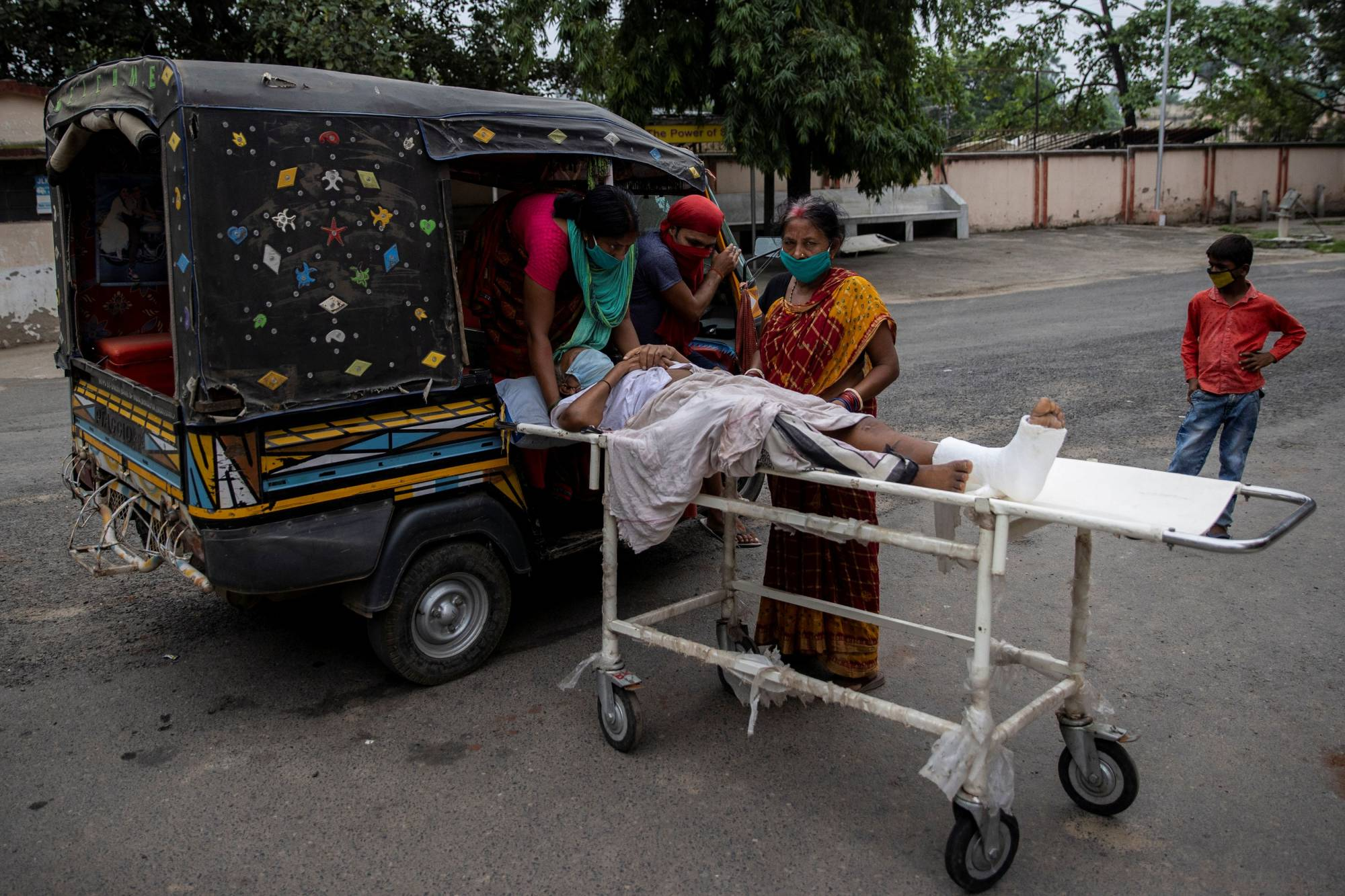 A patient is moved by relatives onto an auto-rickshaw as they take him home following treatment at Jawahar Lal Nehru Medical College and Hospital in Bhagalpur, India. | REUTERS