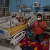A COVID-19 patient lies on a hospital bed as her son sits on the floor beside her in the ICU of Jawahar Lal Nehru Medical College and Hospital.  | REUTERS