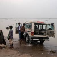 People wash an ambulance on the banks of the Ganges River in Bhagalpur, India.  | REUTERS