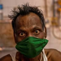 A patient wearing a protective mask looks on after he was admitted to the emergency ward of Jawahar Lal Nehru Medical College and Hospital.  | REUTERS