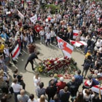 People with old Belarusian National flags lay flowers as they gather at the place where Alexander Taraikovsky died amid clashes protesting last Sunday's presidential election results, during his civil funeral in Minsk on Saturday. | AP