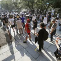 People wait under the scorching sun at in Tokyo's Yasukuni Shrine on Saturday, the 75th anniversary of Japan's surrender in World War II. | KYODO