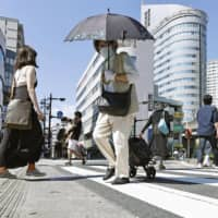 People walk under the blazing sun in Hamamatsu, Shizuoka Prefecture, on Sunday as the city logged a record high of 40.9 degrees.  | KYODO