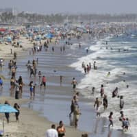 Visitors crowd the beach in Santa Monica, California, amid the coronavirus pandemic on July 12. California is facing a heat wave that could bring dangerously high temperatures and the threat of wildfires throughout the state. | AP
