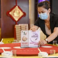 A staff member sets up signs encouraging people not to waste food at a restaurant in Handan, Hebei province, on Thursday.  Chinese diners are being urged to order 'one less plate' after Chinese President Xi Jinping made a speech urging the nation to stop wasting food and embrace thrift. | AFP-JIJI