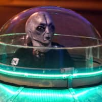 A man in costume rides a UFO-shaped toy car at a park in Cali, Colombia, on July 24 before a night curfew ordered for the coronavirus. | AFP-JIJI