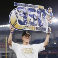 The Fighters' Naoki Miyanishi holds a sign celebrating his 350th career hold on Wednesday in Chiba. | KYODO