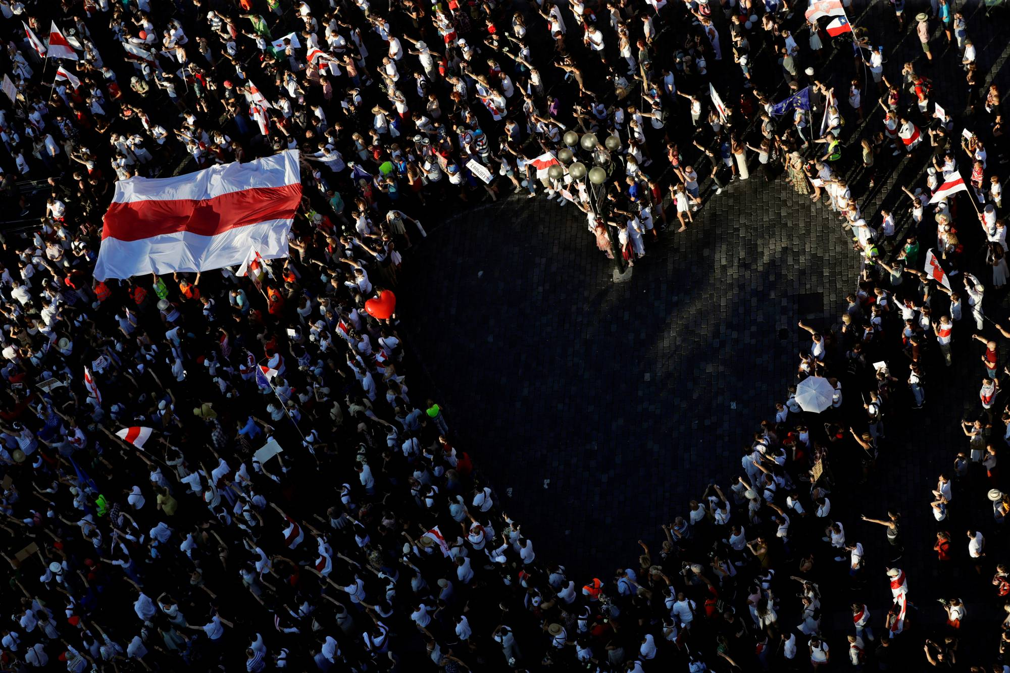 In Prague, a large historical white-red-white flag of Belarus is held up on Sunday next to demonstrators forming a heart during a protest against the results of the Belarusian presidential election. | REUTERS