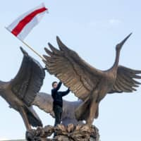 A man waves an old Belarusian national flag, as he stand atop of a sculpture of swans during an opposition rally in front of a government building in Minsk on Sunday. | AP