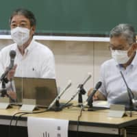 Tenri University vice president Tatsuki Okada (left) speaks in a news conference in Tenri, Nara Prefecture, on Monday. | KYODO