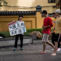 Climate activist Howey Ou (left), 17, stages a protest on a street in Guilin, China, on Aug. 7. | AFP-JIJI