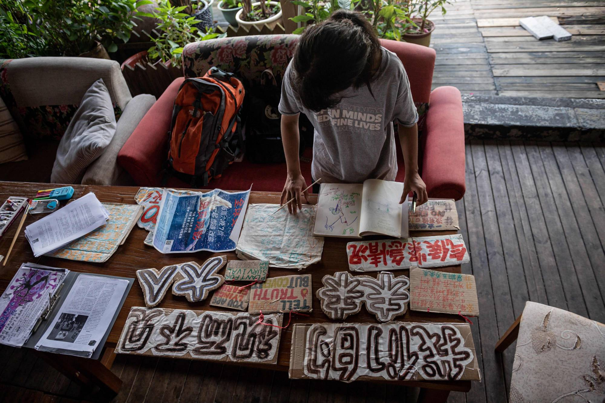 Climate activist Howey Ou, 17, paints signs and placards at her hotel in Guilin, China, on Aug. 7. | AFP-JIJI