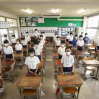 Students stand up and listen to their school song at the beginning of a new semester on Monday in Ogaki, Gifu Prefecture. | KYODO
