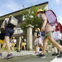 Students arrive Monday at their school in Ogaki, Gifu Prefecture. | KYODO