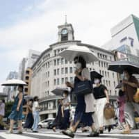 People walk under the glaring sun in Tokyo's Ginza shopping area on Monday. | KYODO