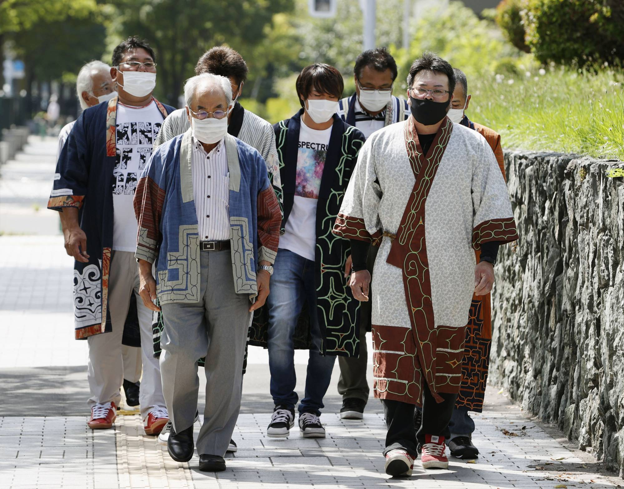 Members of an Ainu minority group walk to the Sapporo District Court on Monday to file a lawsuit against the central government — the first such lawsuit by Ainu people to confirm their indigenous rights. | KYODO