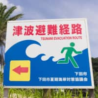Sign of the times: A billboard alerts people to an evacuation route on the Izu Peninsula.  | GETTY IMAGES
