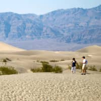 Visitors walk in the Mesquite Dunes in Death Valley National Park, California, in late July.  | REUTERS