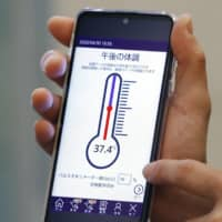 A smartphone app for health management used by novel coronavirus patients at hotels earmarked for those with mild or no symptoms is displayed in Hachioji, Tokyo, on April 30. The Tokyo Metropolitan Government now plans to use the app for patients who choose to stay at home as well. | KYODO