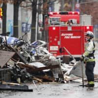 Firefighters inspect collapsed buildings in Sapporo on Dec. 17, 2018, following an explosion the night before. | KYODO