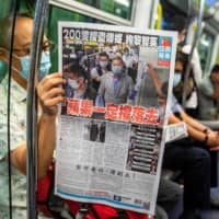 A commuter reads a copy of the Apple Daily newspaper on a train in Hong Kong on Aug. 11.  | AFP-JIJI