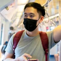 Blending in: A man wears a mask on the train amid the COVID-19 pandemic. According to a survey, Japanese people were more likely to wear a face mask to fit in rather than protect other people from the virus.  | GETTY IMAGES