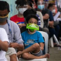 People wait to get tested for COVID-19 at a government facility in Metro Manila, Philippines, on Tuesday. | REUTERS