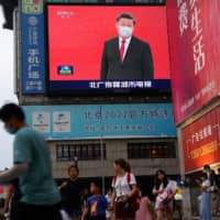 A large screen in Beijing shows a news footage of Chinese President Xi Jinping wearing a face mask.  | REUTERS