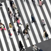 Pedestrians cross a road in the Ginza area in Tokyo. | BLOOMBERG