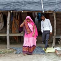 Ashish Kumar walks with his mother, Bittu Devi, outside their house. | REUTERS