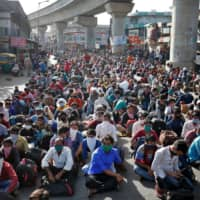 Migrant workers and their families wait for transport to reach a railway station to travel to their home state of northern Uttar Pradesh after a COVID-19 lockdown was eased in May.  | REUTERS