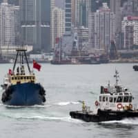 A Chinese fishing vessel attempts to depart for the disputed Senkaku Islands as a police boat (right) intercepts it in Hong Kong in November 2013. | REUTERS