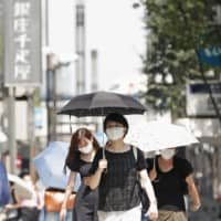 People walk in Tokyo's Ginza district with parasols amid the scorching summer heat Wednesday. | KYODO