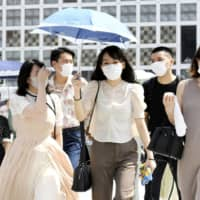 People walk at a scramble intersection in front of Tokyo's Shibuya Station on Tuesday, amid the scorching summer heat. | KYODO