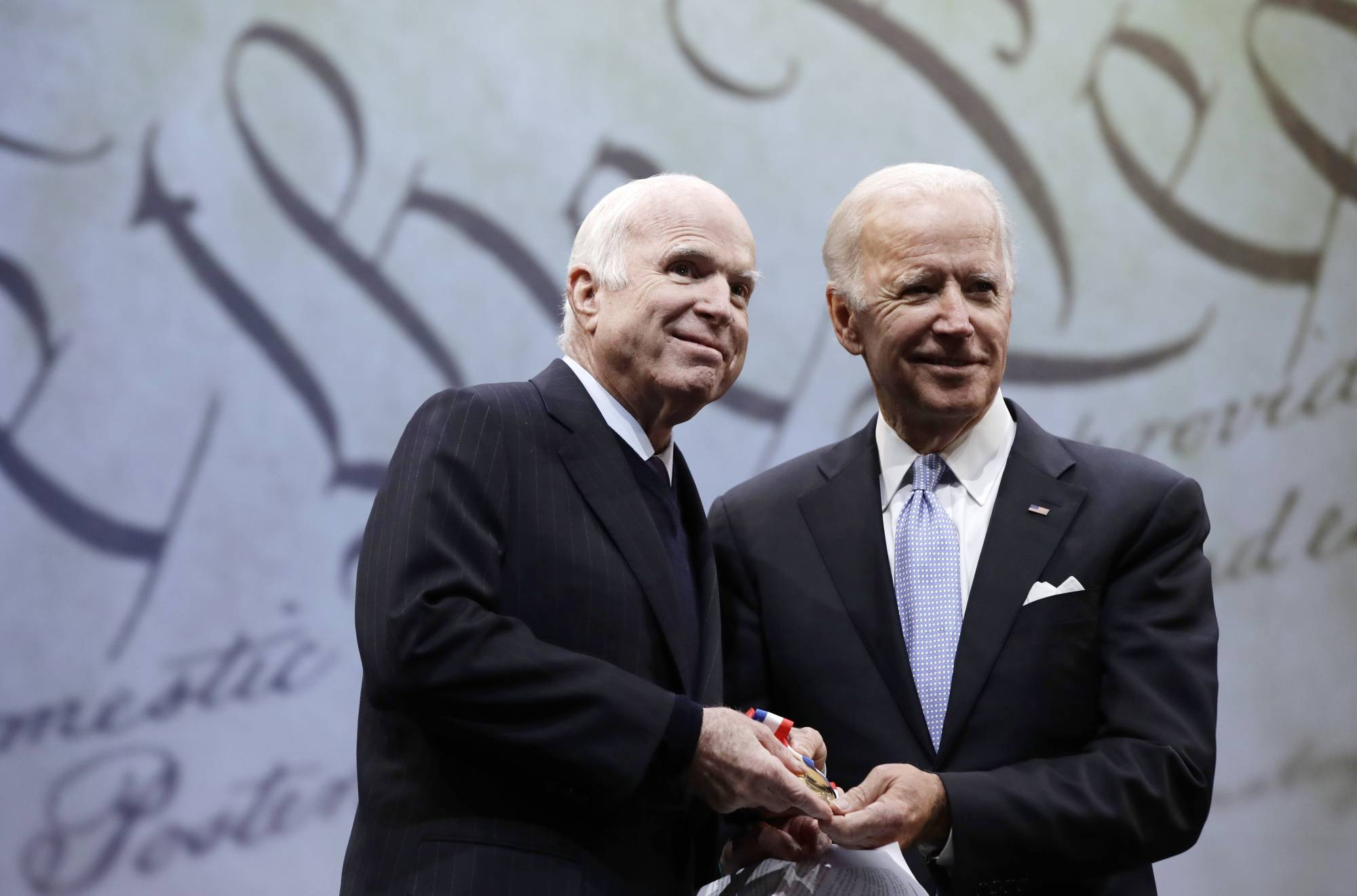 FILE - In this Oct. 16, 2017, file photo Sen. John McCain receives the Liberty Medal from former Vice President Joe Biden in Philadelphia in 2017. | AP