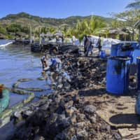 People clean up leaked oil on the coast of Mauritius on Aug. 14. | JAPAN INTERNATIONAL COOPERATION AGENCY / VIA KYODO