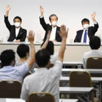 Members of the Democratic Party for the People endorse a plan to dissolve the party for a merger with the Constitutional Democratic Party of Japan, during a meeting in Tokyo on Wednesday. | KYODO