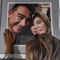 Glenda Amaya gently touches a picture of her deceased husband, German Amaya, inside her home near Miami. German died in a Florida hospital after a long battle with COVID-19. | AFP-JIJI