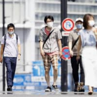 People walk in the Shinjuku area of Tokyo on Wednesday amid scorching summer heat. | KYODO