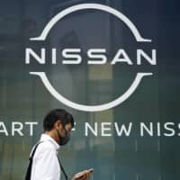 A man walks past Nissan's new logo at one of the automaker's showrooms in Tokyo last month. | AP