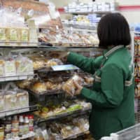 A store clerk stacks shelves at a 7-Eleven convenience store in Tokyo. | KYODO
