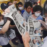 People gather to get an extra edition of a newspaper that was distributed Thursday in Seto, Aichi Prefecture, the hometown of Sota Fujii, who has become the youngest shogi player to win two of the game's major titles. | KYODO