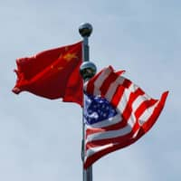 Chinese and U.S. flags flutter near The Bund before the U.S. trade delegation meet their Chinese counterparts for talks in Shanghai in July 2019. | REUTERS